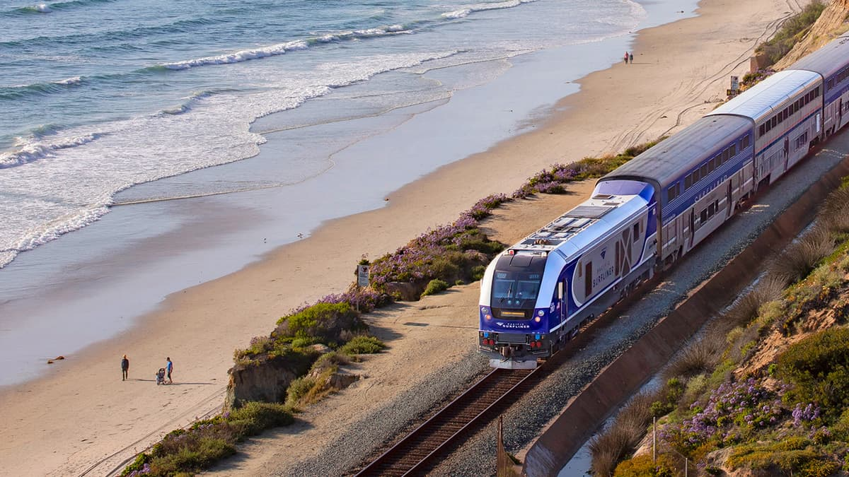 A photograph of a train traveling by a beach.