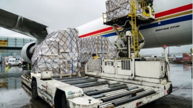 Pallets of cargo are unloaded from a big plane.