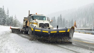 Plow clearing snowing Idaho highway.