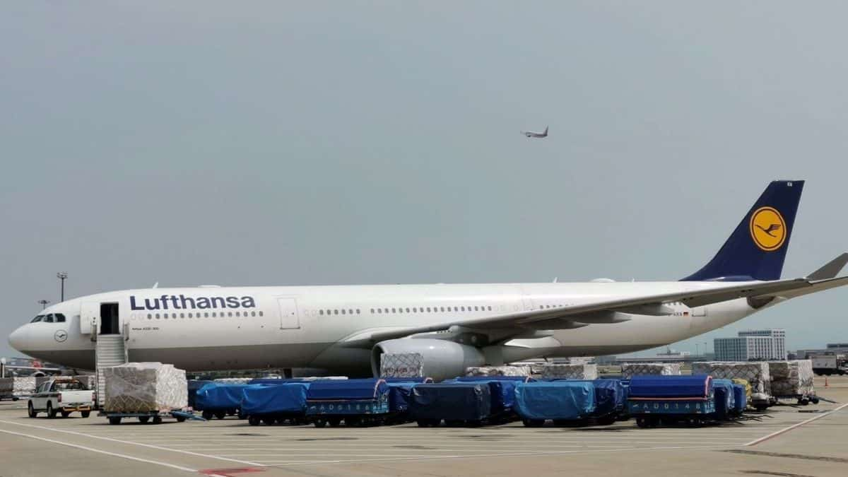 A big white jet with blue tail surrounded by cargo carts on the ground.