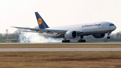 A white Lufthansa plane touches down on runway.
