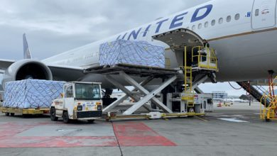 A big white jet gets loaded with pallets of cargo.