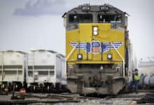 A photograph of a man boarding a freight train.