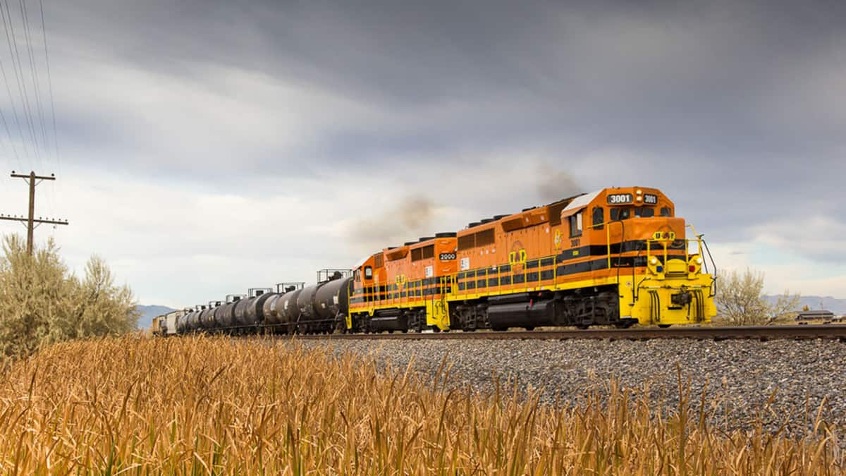 A photograph of a train hauling tank cars across a field.