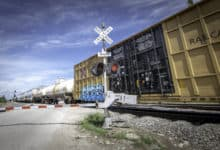 A photograph of boxcars and tank cars at a rail crossing.