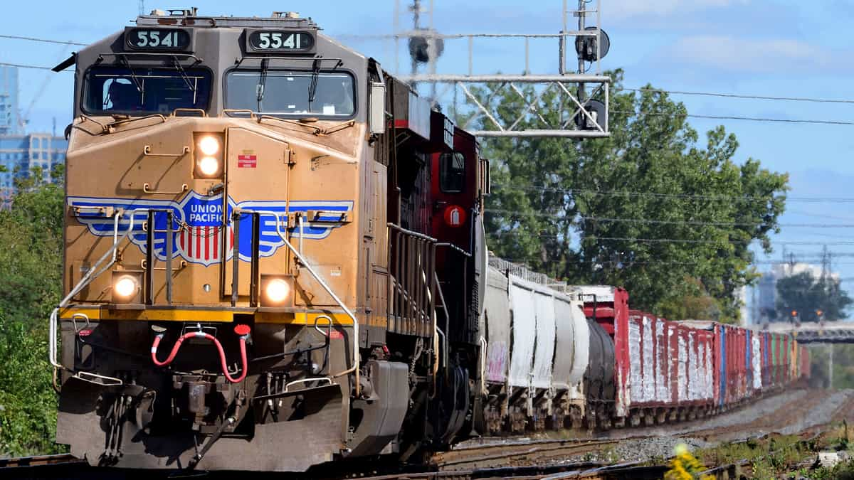 A photograph of a train locomotive pulling railcars on a sunny day.