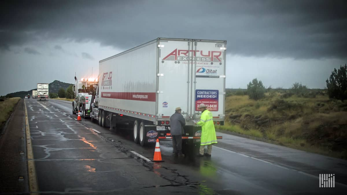 Tractor-trailer stuck on side of wet highway with storm cloud ahead.