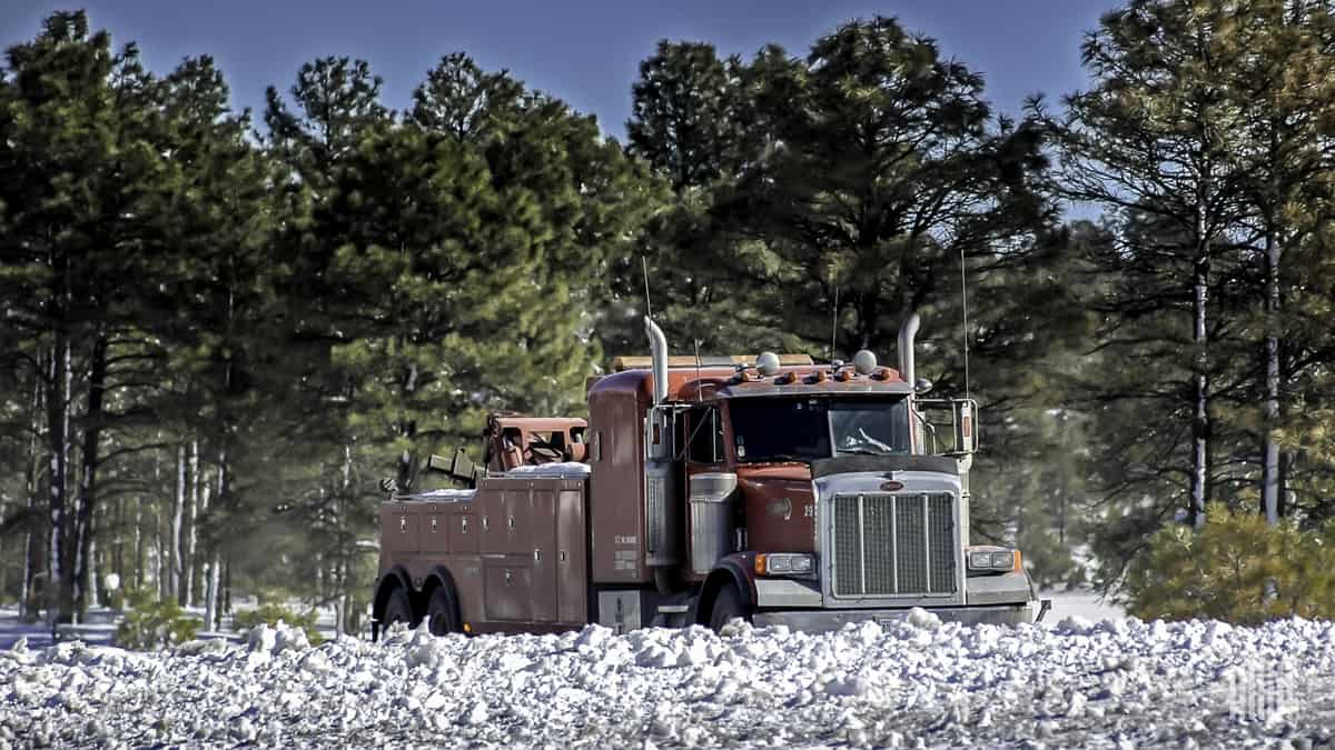 Flatbed truck on road with snow-covered hillside.