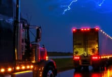 Tractor-trailers on wet highway with lightning across the sky.