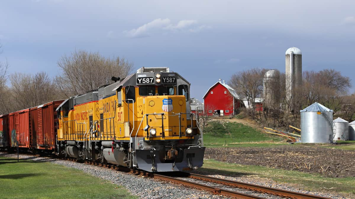 A photograph of a train traveling past a farm.