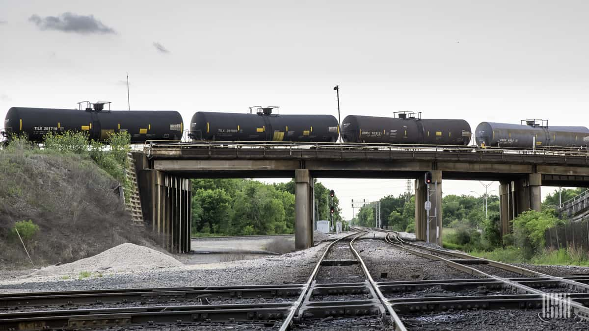 A photograph of tank cars crossing a bridge.