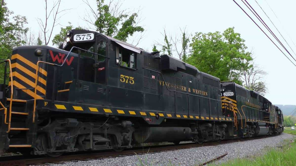 A photograph of a train locomotive. There are trees behind the train.