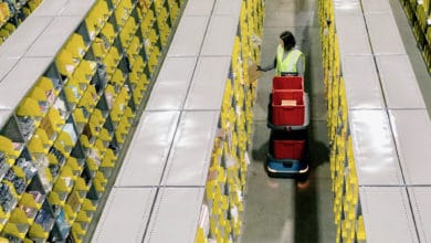 A warehouse worker with a robot at a Shopify fulfillment facility.