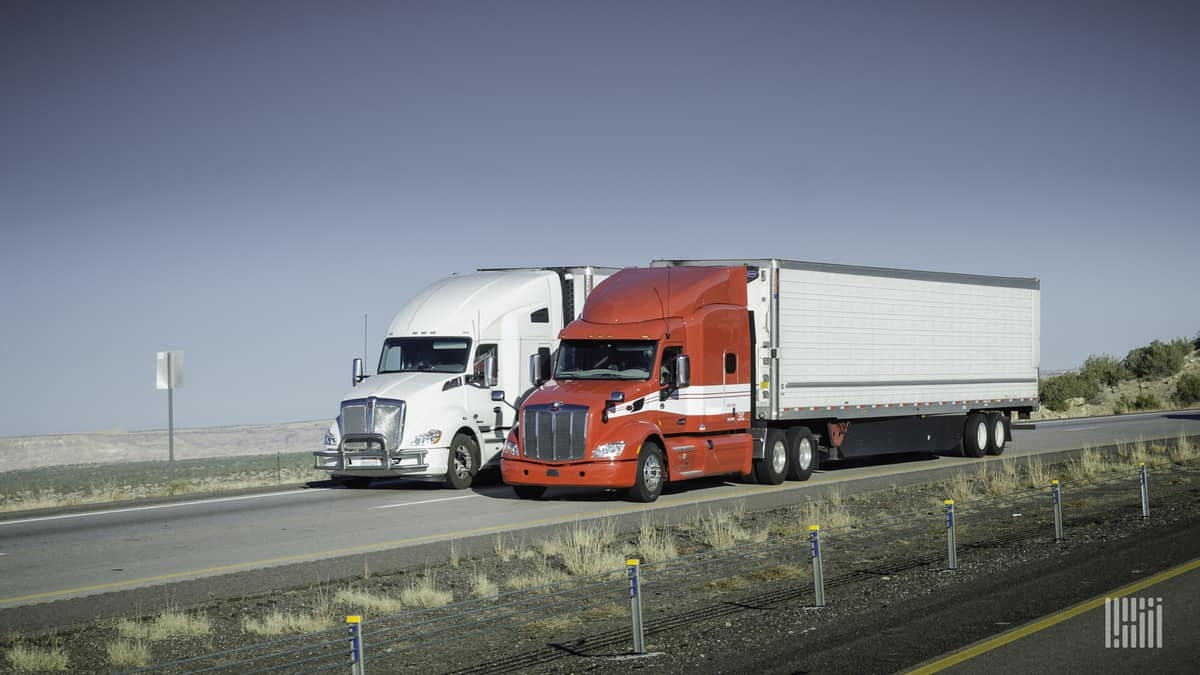 Trucks move along a divided highway.