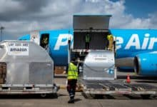Light blue Amazon Prime plane with cargo door open, waiting for a load.