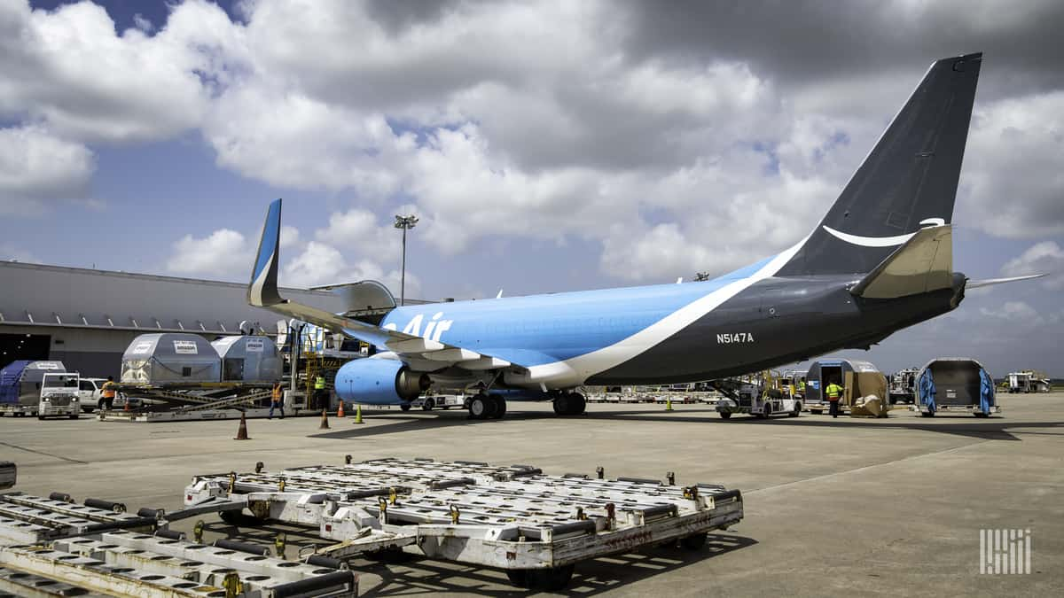 Light blue Amazon plane sits at gate waiting to be loaded.