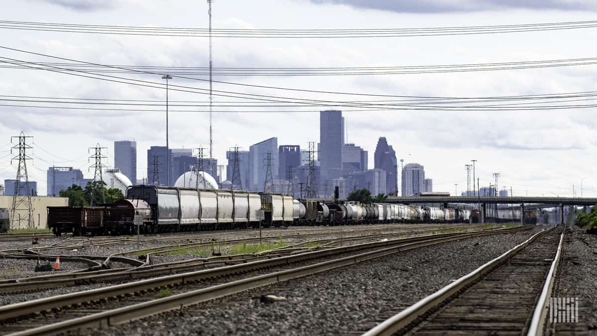 A photograph of a rail yard with train tracks and a train. There is a city with skyscrapers far in the distance behind the train.