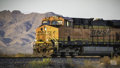A photograph of a freight train locomotive. In the background is a mountain range in the desert.