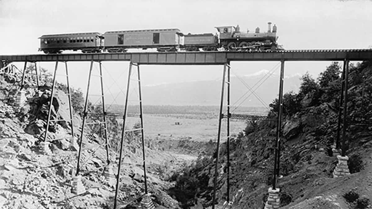 High Bridge Near Buena Vista between 1880 and 1897. A steam engine, coal car, box car and passenger car comprise the train crossing the bridge.