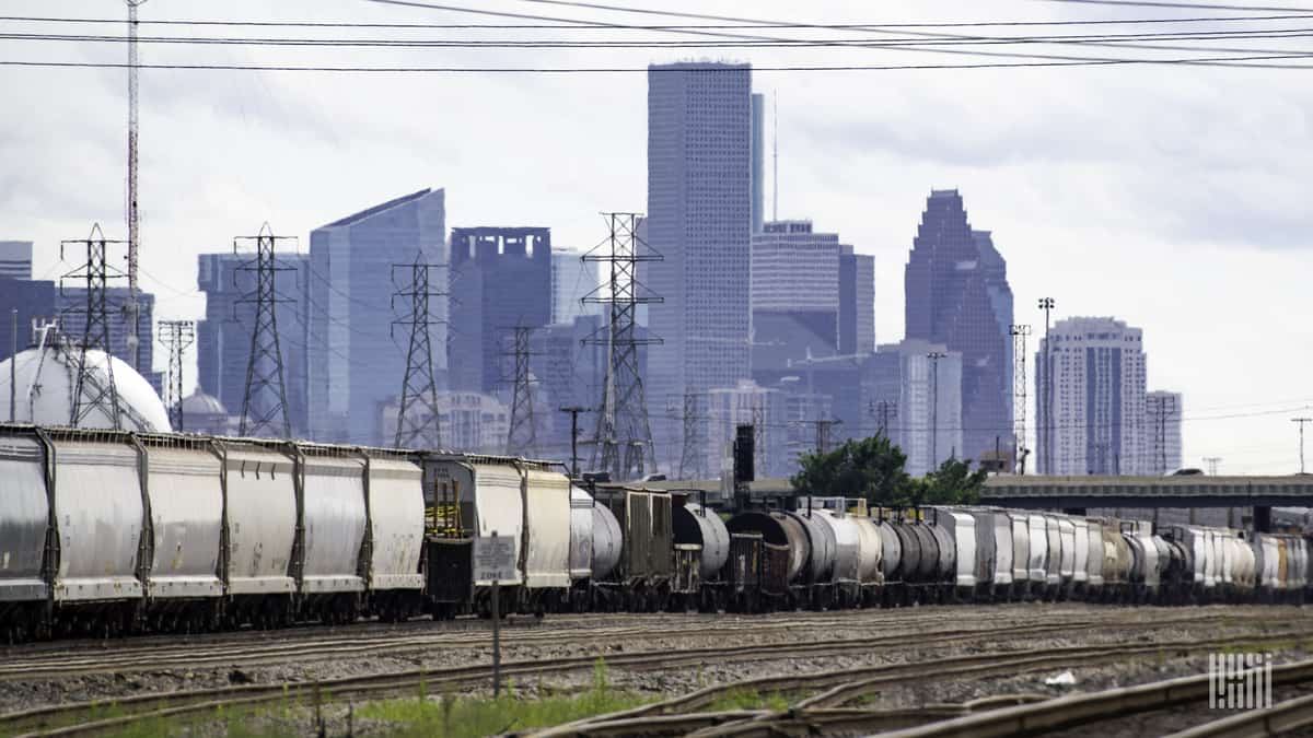 A freight train sits in a marshalling yard near a major city.