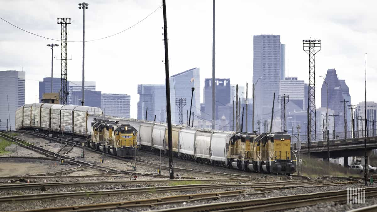 Two Union Pacific freight trains move on parallel tracks in a major city environment. (Photo: Jim Allen/FreightWaves)