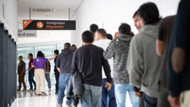 A photograph of people waiting in a long line inside a hallway.