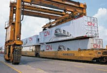 A photograph of tall cranes lifting an intermodal container. That container is stacked on top of another container.