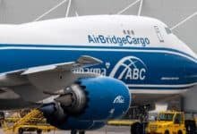 A blue-and-white 747 jumbo cargo jet parked at airport.
