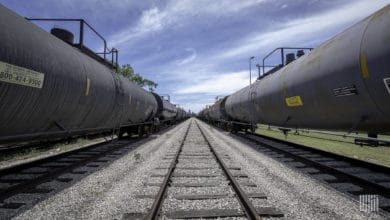 A photograph of tank cars in a rail yard. The tank cars are in lined up left and right.