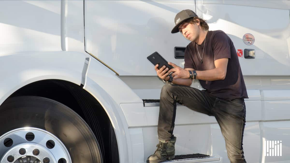 Driver standing outside of white truck using tablet