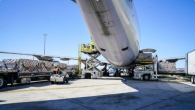 Large cargo plane being loaded, view from underbelly at tail end.