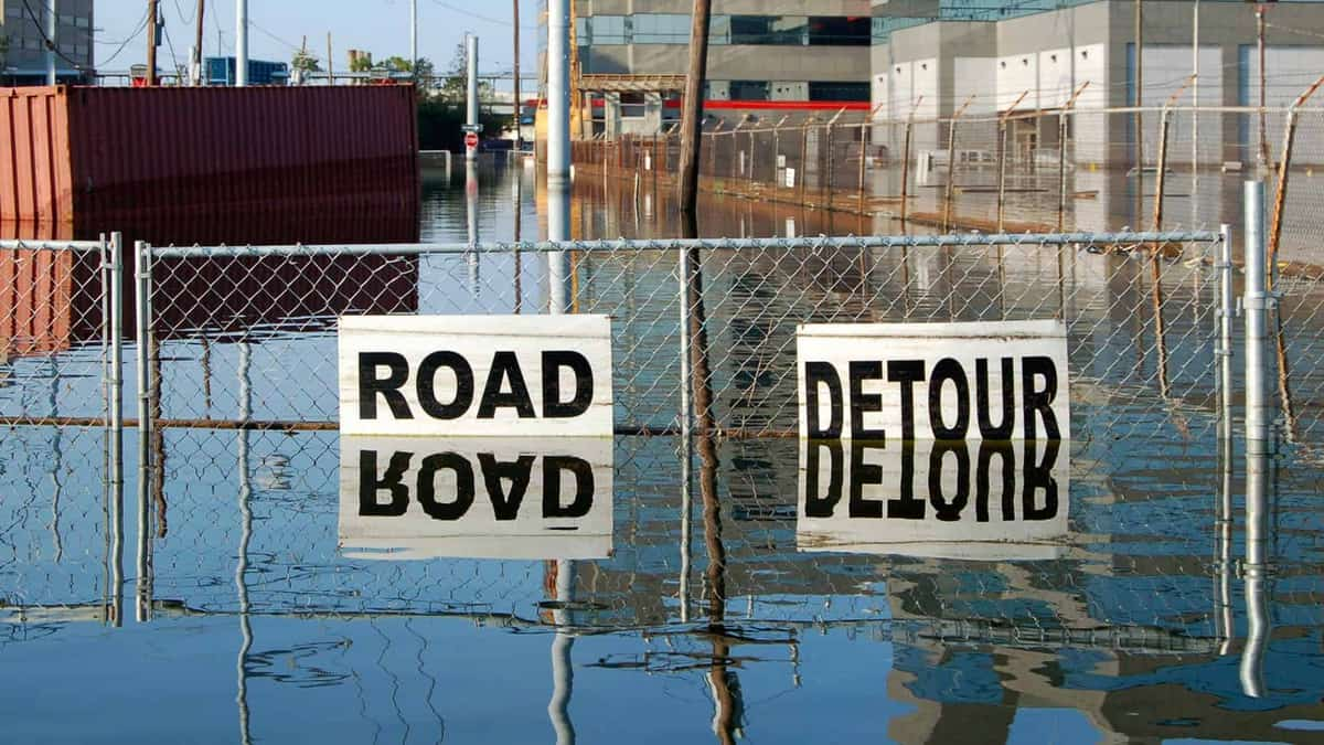 """Flooded road with """"Road Closed"""" signs."""