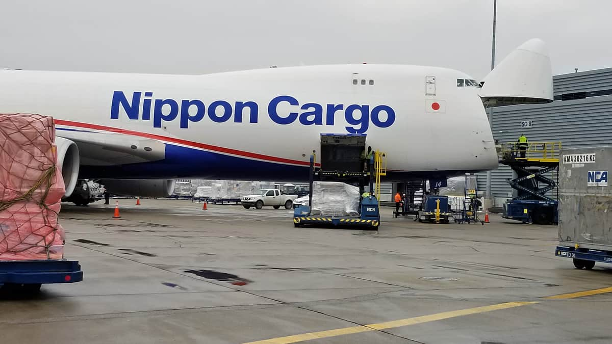 Big white 747 freigher with nose cone up to load cargo.