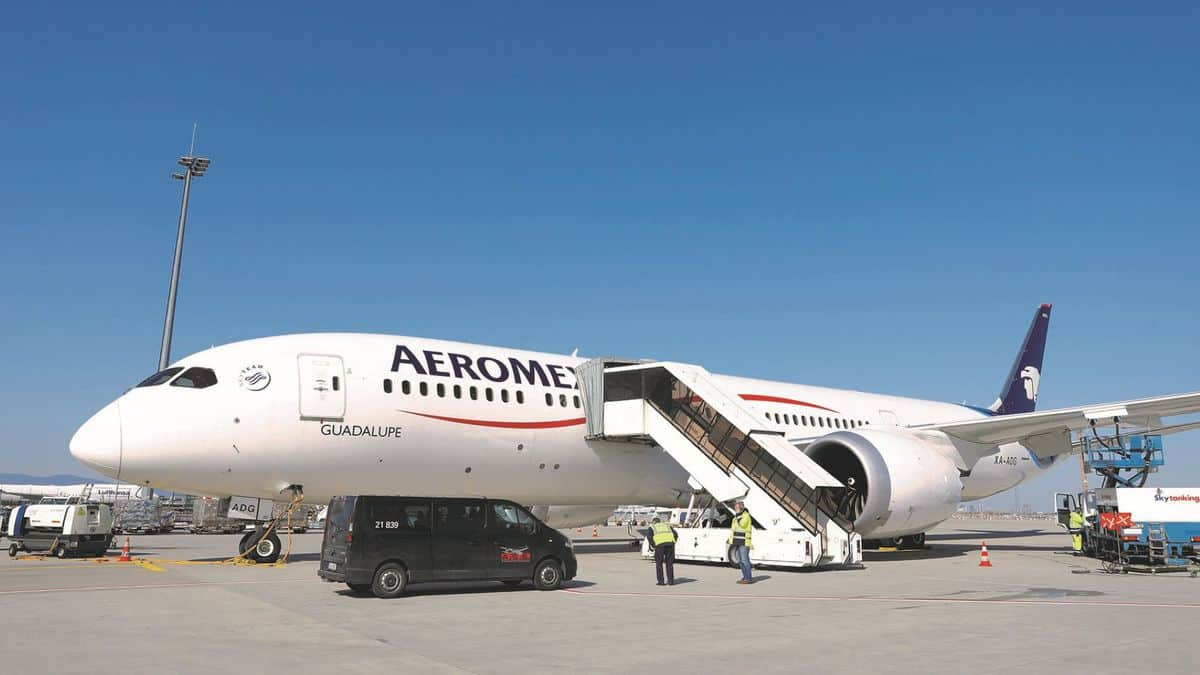 A white passenger jet with stairs leading up to front door.