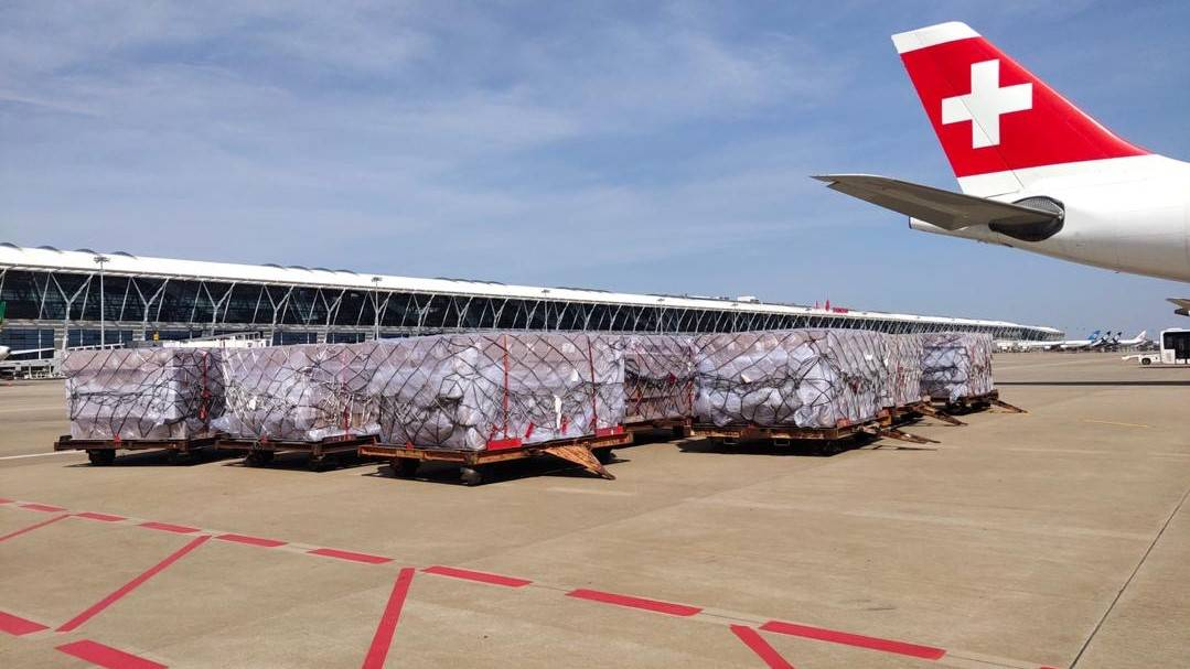 Cargo pallets on the tarmac and the tail of Swiss Air Lines with white cross on it