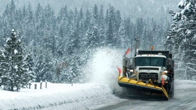 Plow clearing snowy Idaho highway.