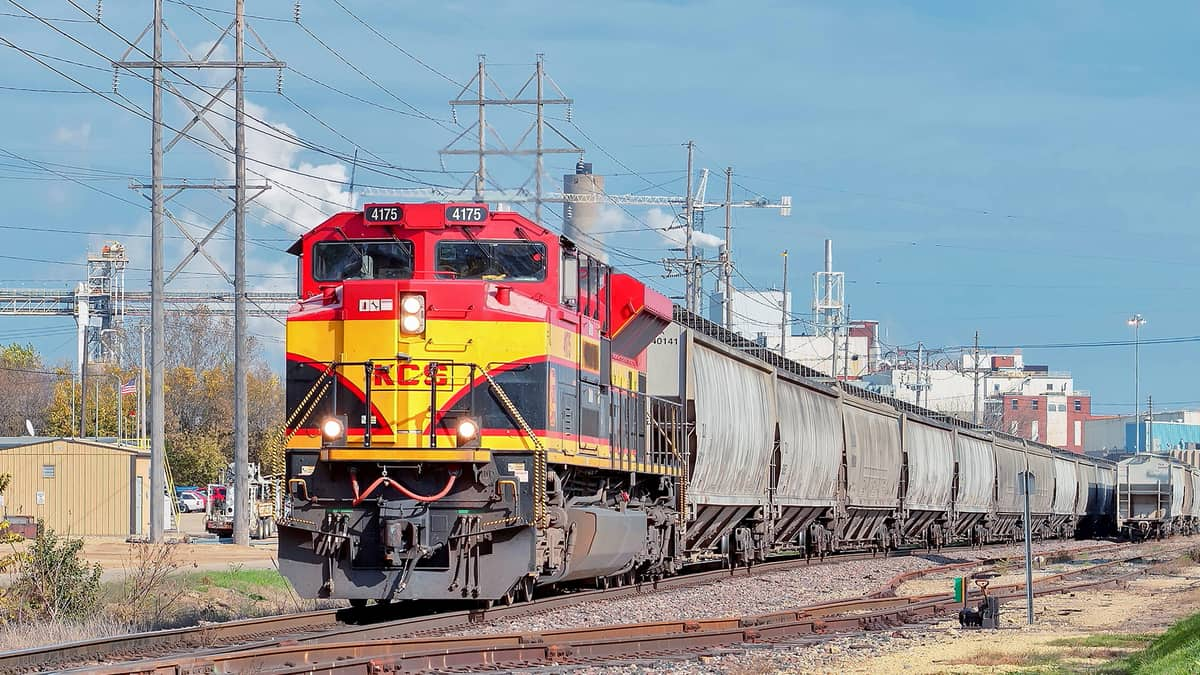 A photograph of a train hauling railcars.