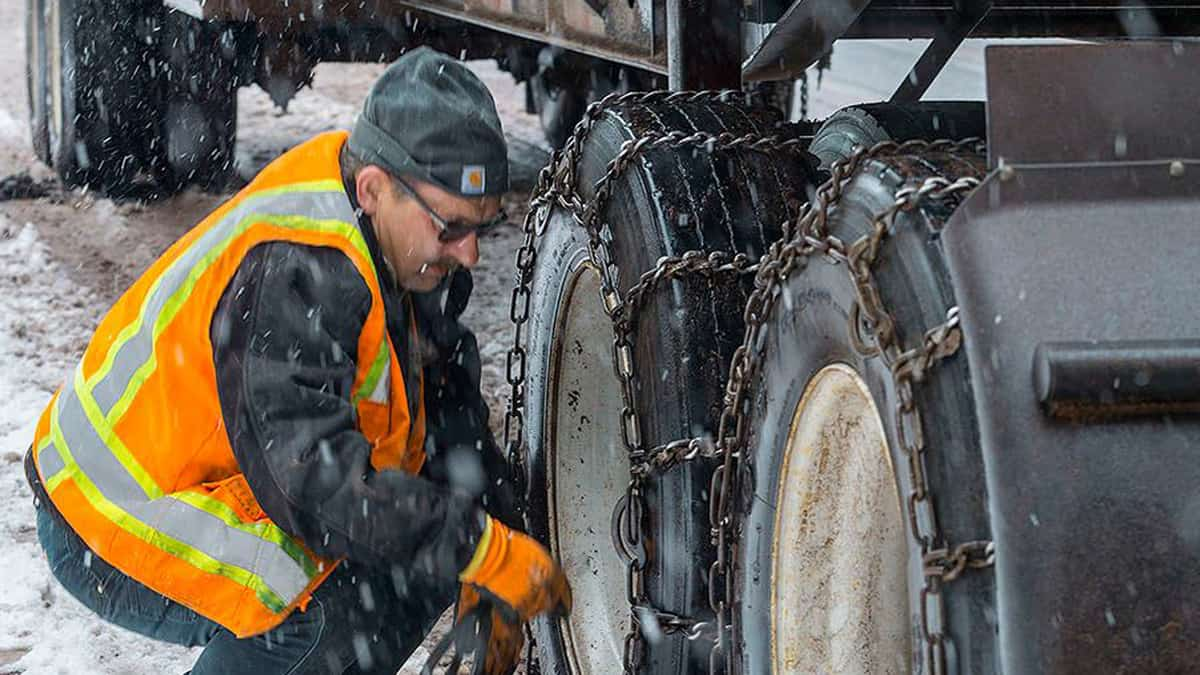 Truck driver putting chains on his tires in the snow.