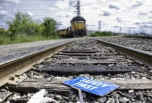 A photograph of a rail track close up. On the track is a paper sign that says, Safety First. In the distance is a freight train locomotive.