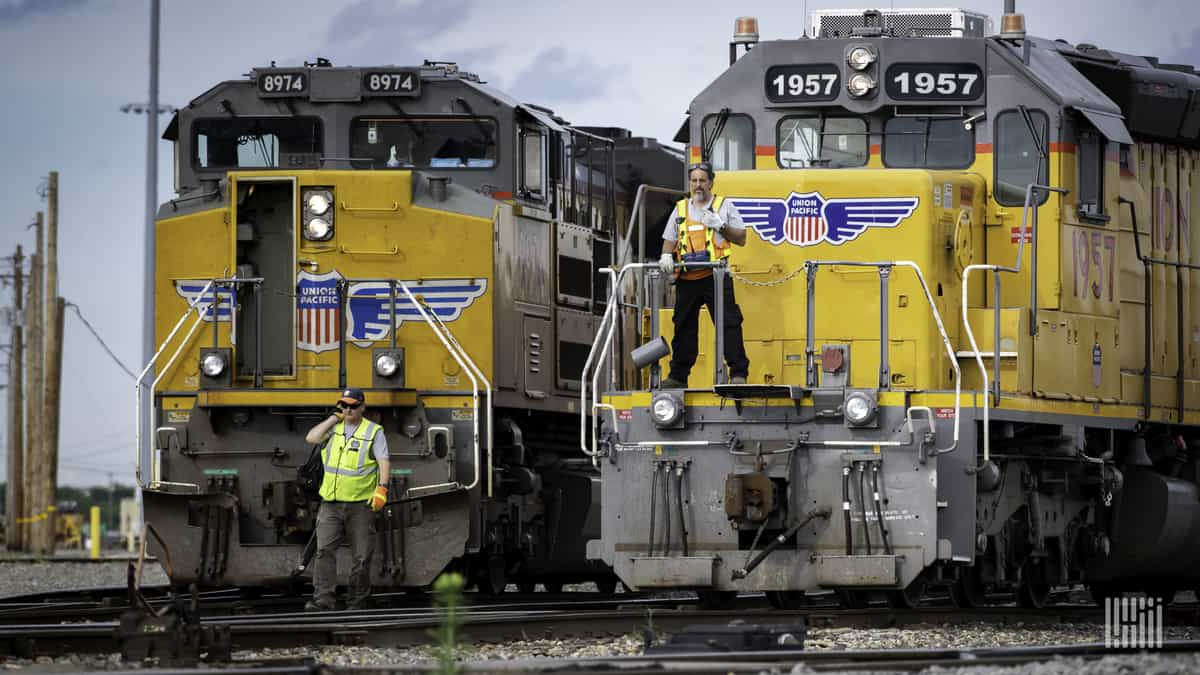 A photograph of two train locomotives. There are two men standing in front of each train.