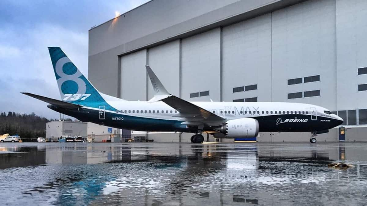 A blue and white 737 MAX next to a hangar at a Boeing facility.