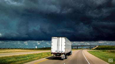 Tractor-trailer on highway with thunderstorm in the distance.