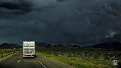 Tractor-trailer heading down highway with dark thunderstorm ahead.