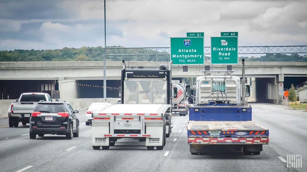 two trucks travel down a highway