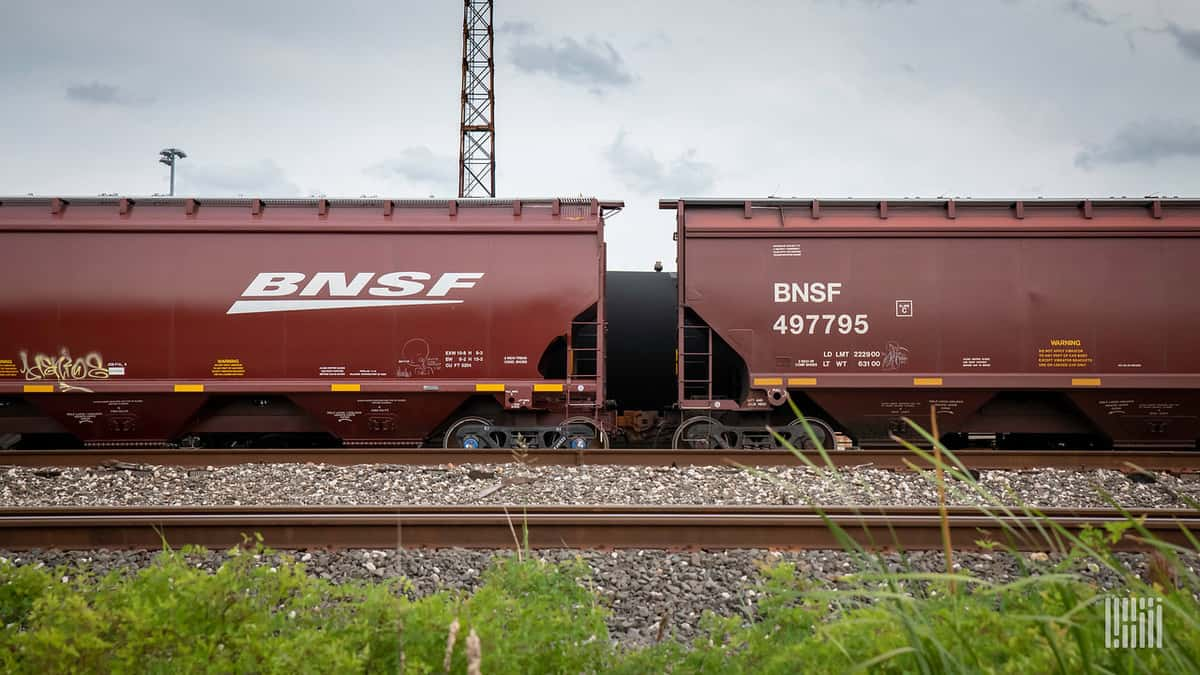 A photograph of two railcars in a rail yard.