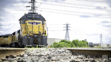 A photograph of a train in a rail yard. There are electricity lines above the train and behind it.
