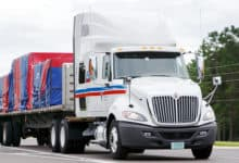 A tractor-trailer of CT Transportation hauls a flatbed load. TFI International acquired nearly all of CT assets from Comcar.