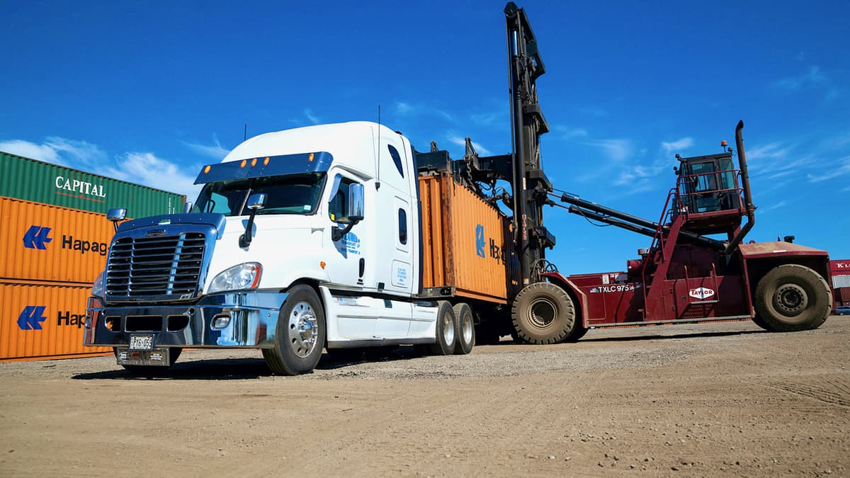 A shipping container is loaded onto a truck from Gusgo Transport, a Canadian trucking company recently acquired by TFI International.