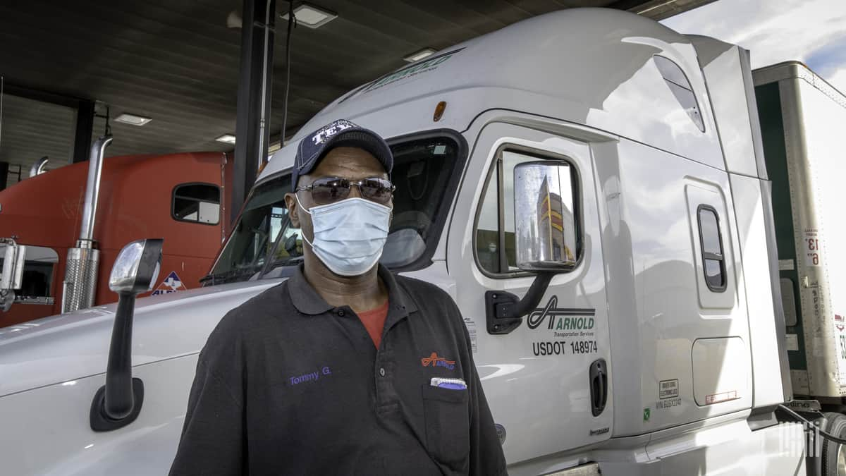 A truck driver uses personal protective equipment as he wears a medical face mask