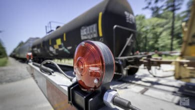 A photograph of a tank car by a rail crossing.